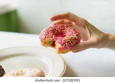 A female hand takes a donut with a pink glaze from the plate