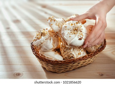 female hand takes  meringue from basket on  wooden table.  closeup