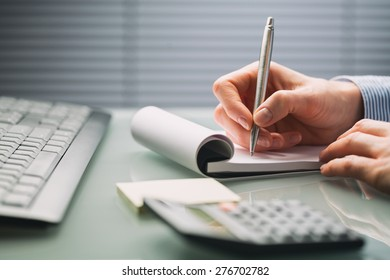 A female hand takes notes on a paper notebook over a busy office desktop. Low angle closeup image.