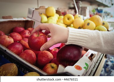Female hand taking fruit from a shelf