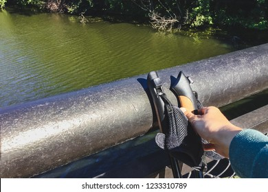 Female hand taking Nordic walking poles standing up against bridge railing. Concept of healthy, active lifestyle. POV shot