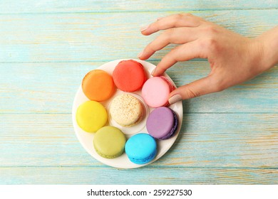 Female hand taking tasty colorful macaroons from small plate on color wooden background