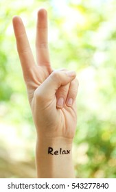 Female hand with tattoo word RELAX, outdoor