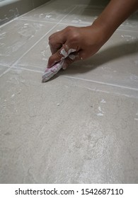 Female hand technician use of rubber flooring on white color of new grout tile on tile grout.Grouting ceramic tiles. Tilers filling the space between tiles using a rubber trowel.