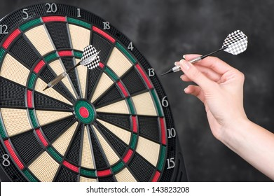 Female hand throwing darts at dartboard
