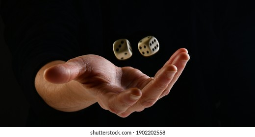 Female hand throwing two white dice in the air on black background. Game with dice, Hazard, Cho-Han Bakuchi, Under-Over 7, Mexico, Shut the Box. Gambling luck concept: bet, risk, have luck, win. lucky