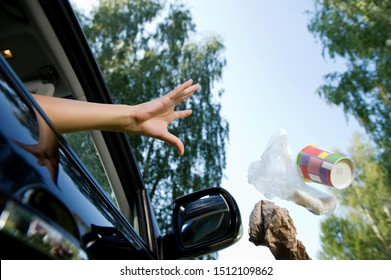 a female hand throws a handful of garbage accumulated in the car through the open window of the car - coffee glasses, bags, crumpled paper. Flying objects are slightly blurred to enhance the effect of