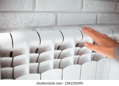 Female hand touches the radiator.