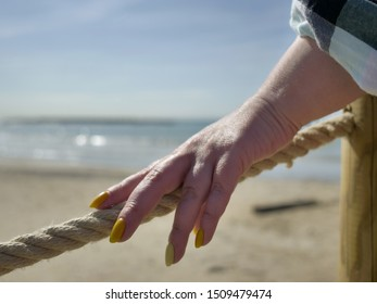 A female hand touches a rope stretched on a beach pier near the sea, the passage is closed, the end of vacation and the beach season