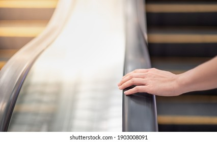 Female hand touching escalator handrail while using escalator in shopping mall or public area for moving to another floor. For the concept shopping in public area and shopping mall.