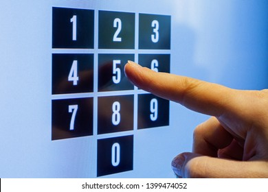 Female hand touching a screen with numbers. Dial passcode.