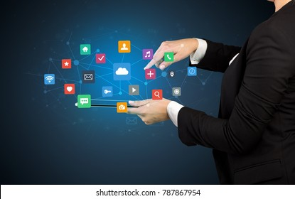 Female hand touching tablet with application icons above