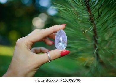 Female hand with transparent amethyst quartz yoni egg