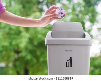 female hand trowing a paper into a garbage bin on bokeh background. cleaning concept.