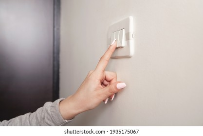 Female hand turning an electricity light switch on the wall.