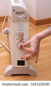 Female hand turning on thermostat on electric heater inside room interior