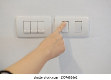 Female hand turns off the light switch in the room
