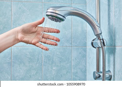 Female hand under the stream of water from the shower head, fixed in the holder, checks the water temperature in the bathroom with blue tiles.