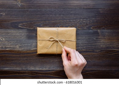 female hand unpacking gift box wrapped with craft paper and flowers on the wooden table top view. Gift for any holiday.
