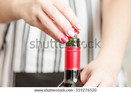 Female hand unscrews the screw cap red wine bottle