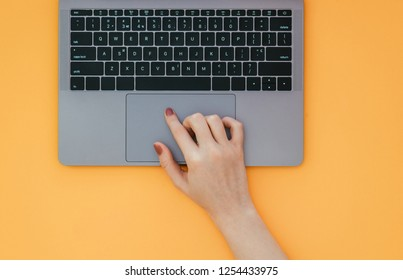 Female hand uses a touchpad on a laptop on a yellow background. The finger on the touchpad has a top view. Flat lay