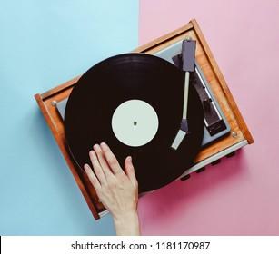 Female hand uses vinyl player, conceptual photo, DJ, minimalism, top view
