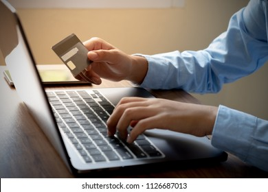 Female hand using credit card for online shopping and payment with laptop computer. Electronics and digital banking concept.