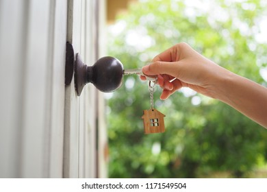 The female hand is using the key to open his own house. New home, home and homeownership concept