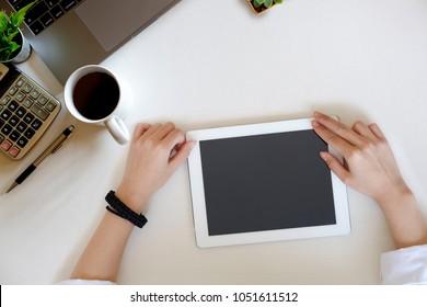 Female hand using mockup tablet on white wood desk.