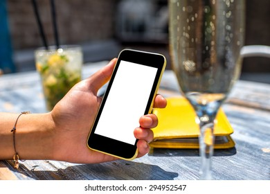 Female hand using a phone with isolated screen on wooden vintage table holding a glass with mohito