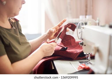 Female hand using scissors for cutting off textile piece. Close up side view of woman, engaging in sewing process at workshop. Blurred background. Handicraft, hobby, self-employment, business concept.