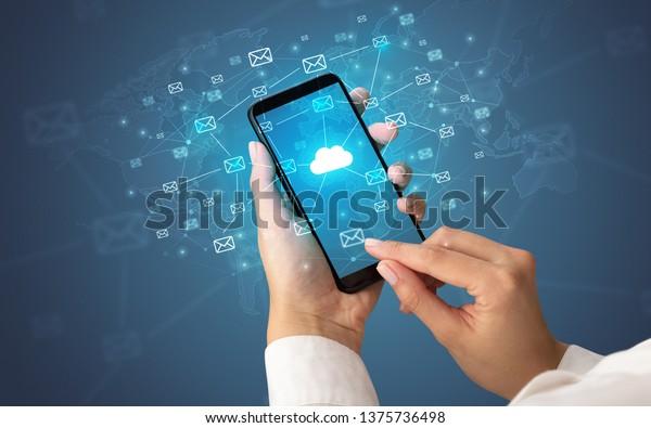 Main féminine utilisant un smartphone avec cloud, message et concept global