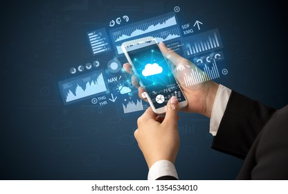 Female hand using smartphone with financial tracking concept illustrated by graphs and symbols