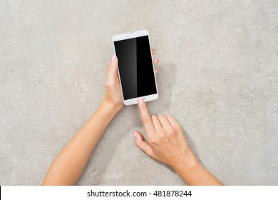 Female hand using white smart phone