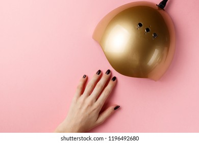 Female hand and UV lamp lights for nails on pink background. Top view. Flat lay. Copy space. Minimal creative concept. Pink background in pastel colours