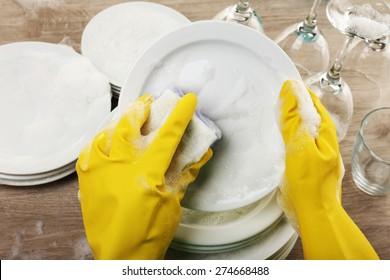 Female hand washing dish close up
