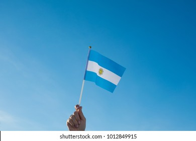 Female hand waving a Argentina flag on a blue sky