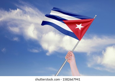 Female hand is waving Cuban Flag against blue sky with clouds. Realistic reflections and textures with high resolution. 3D rendering.