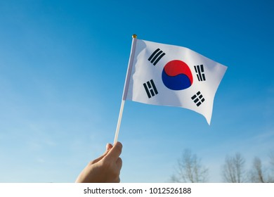 Female hand waving a South Korea flag on a blue summer sky
