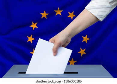 female hand in a white blouse drops a ballot paper in a ballot box against the background of the European Union flag and modern architecture, the concept of elections to the European Parliament