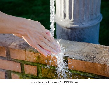Female hand. Woman washes her hands under flowing water in a city fountain at the sports ground. Clear water is available everywhere in Spain. Clean hands and fresh skin.