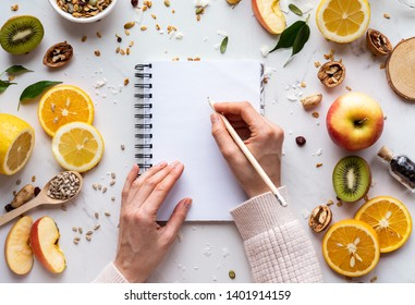 Female hand write in notebook on healthy food background, women diet nutrition recipe menu, fresh summer fruit granola seeds on white table organic super food, health care detox, top view, copy space - Shutterstock ID 1401914159