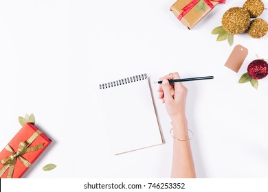 female hand writes in a notebook with a pencil on a white table among New Year's gifts, a view from above