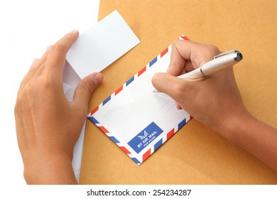 Female hand writing address on envelope holding a business card