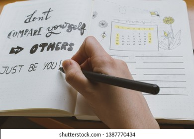 """Female hand writing in a bullet journal a self-esteem quote: """"don´t compare to others, just be you"""" with beauty lettering style"""