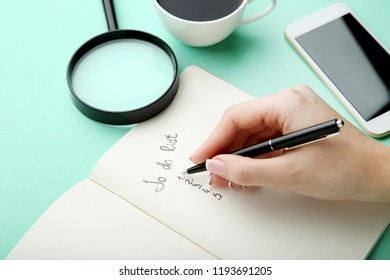 Female hand writing to do list in notepad on mint background