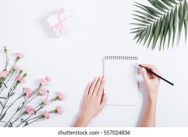Female hand writing in a notebook at the desk, top view. On the white table lay flowers and a box with a gift and ribbon.