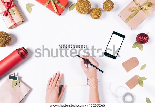 Female hand writing in notebook on white table among the Christmas decorations, top view