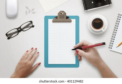 Female hand writing on notebook surrounded with office accessories. Top view of work desk. Coffee, glasses, pencil, mouse, paper, camera beside.