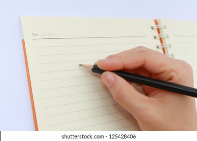 female hand writing on notebook.Note book it can record what you want by writing on it